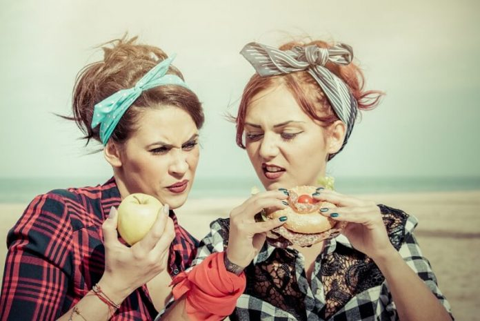junk food vs healthy food: ywo girls making difference between foods